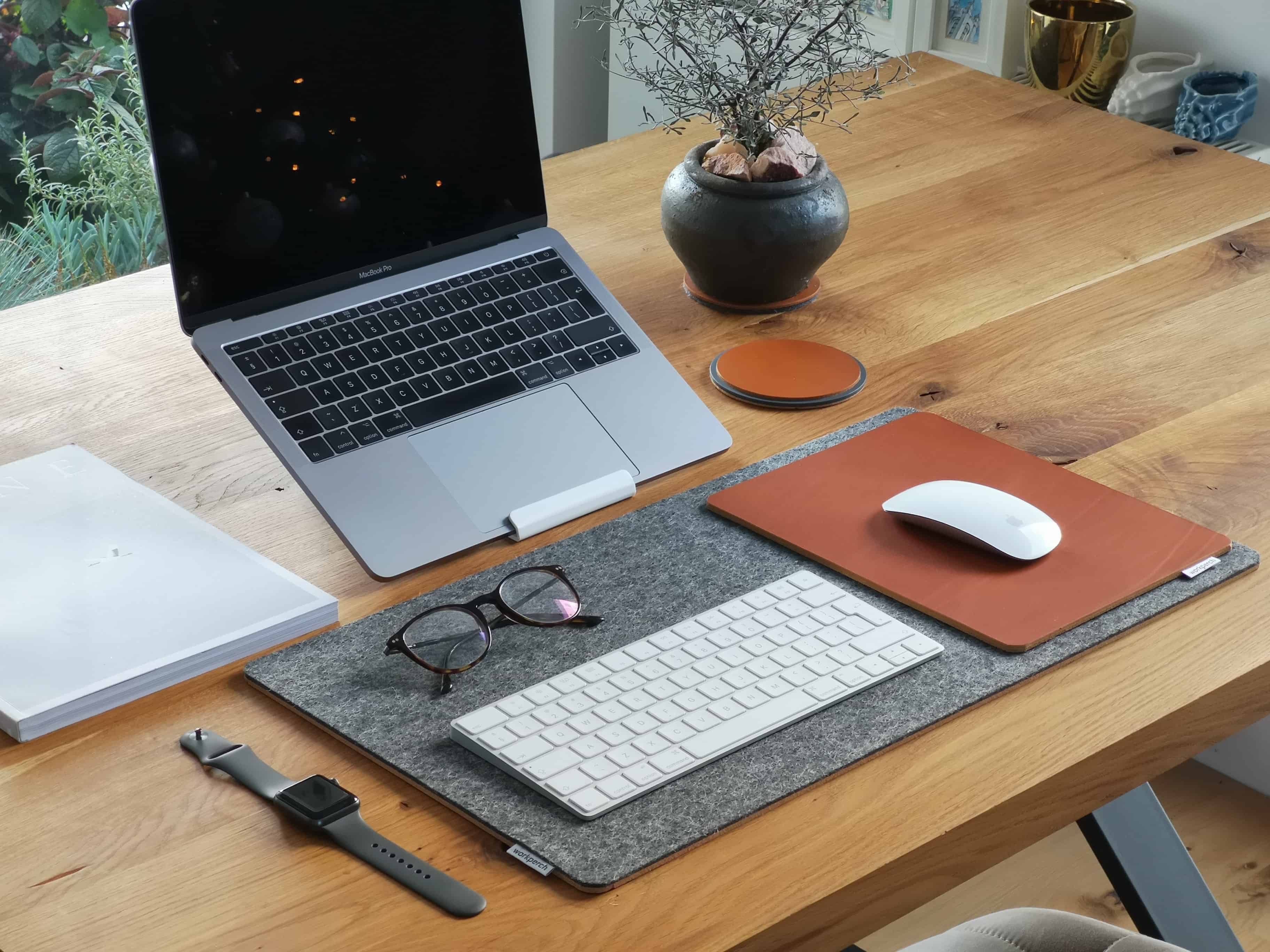 macbook on stand, mouse and keyboard on desk mat
