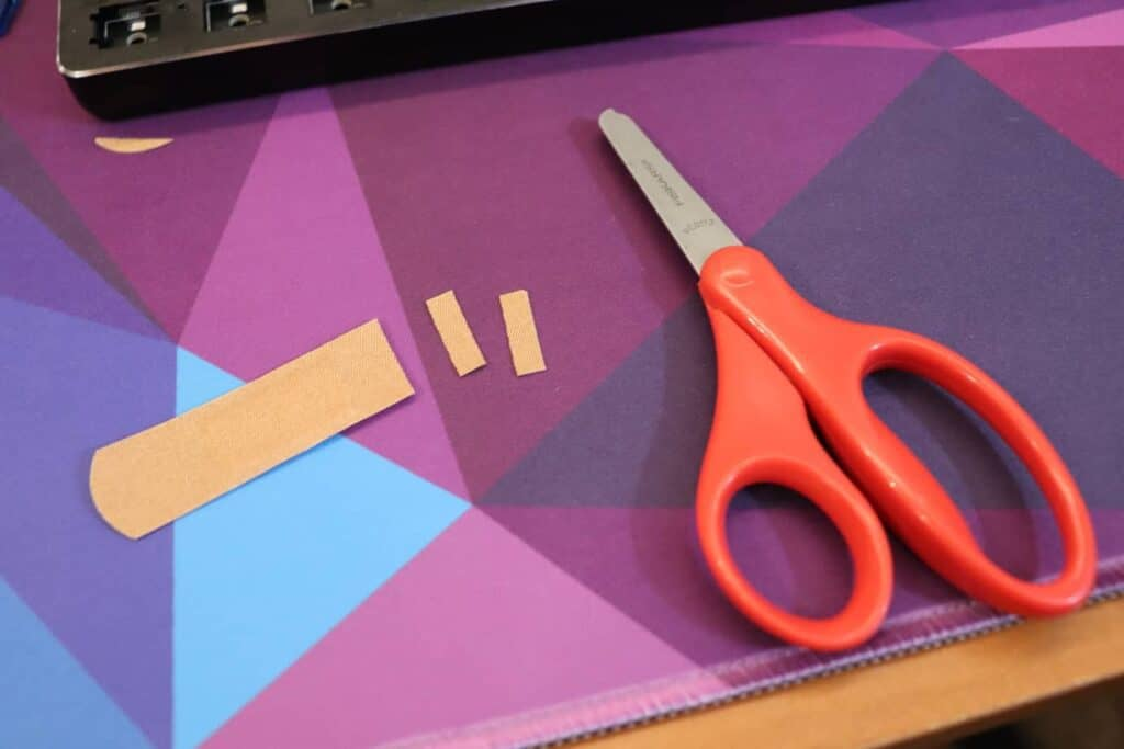 band-aid strips being cut to mod mechanical keyboard stabilizers
