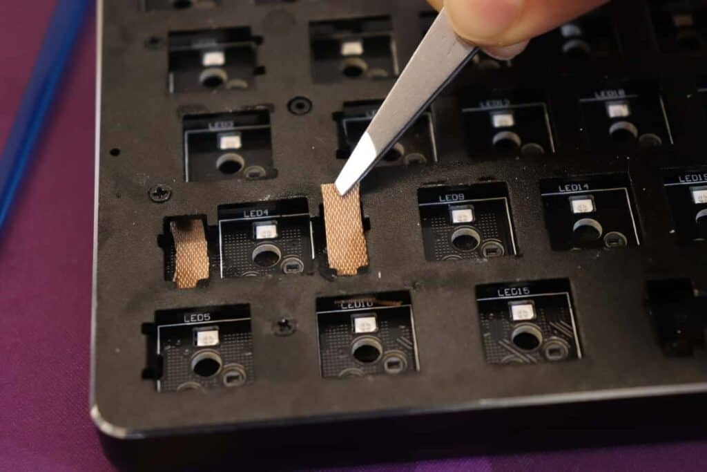band-aids being applied to mechanical keyboard PCB