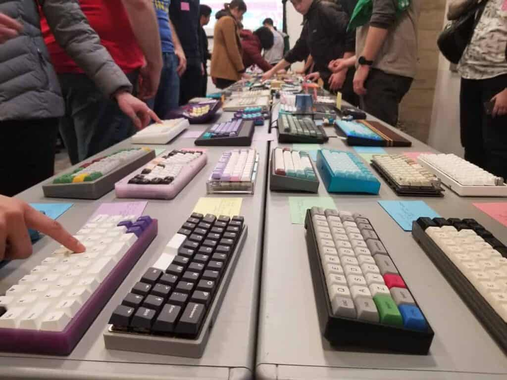 Table full of mechanical keyboards that are custom made.
