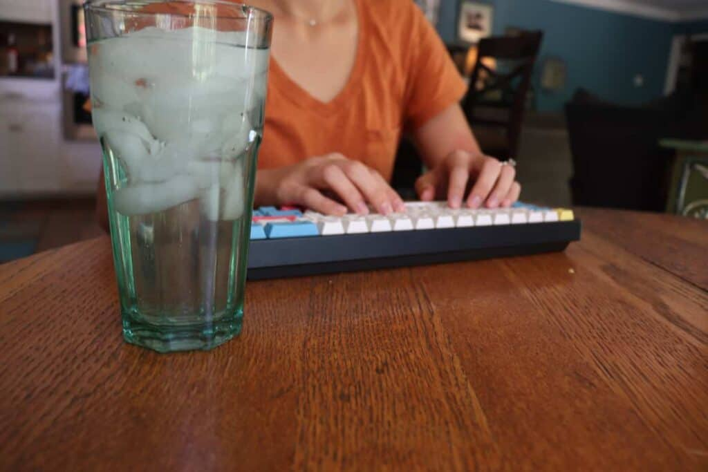 Glass of water by mechanical keyboard