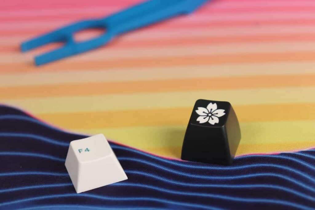 Different kinds of double-shot keycaps next to each other on a deskmat.
