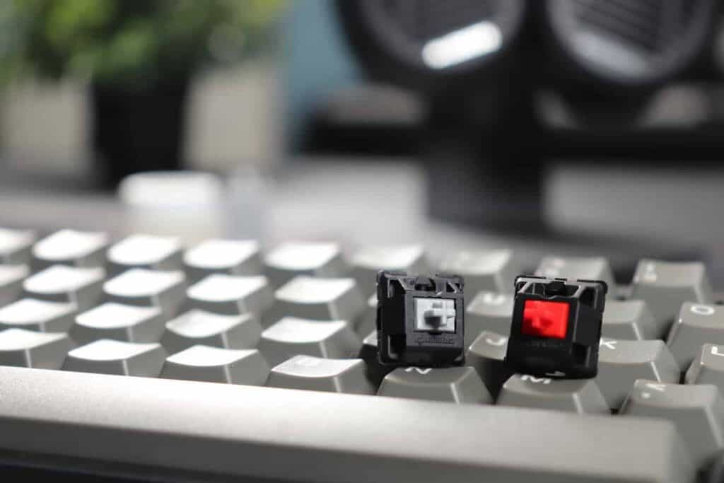 Close up of Cherry MX Speed Silver switch next to Cherry MX Red switch on keyboard.
