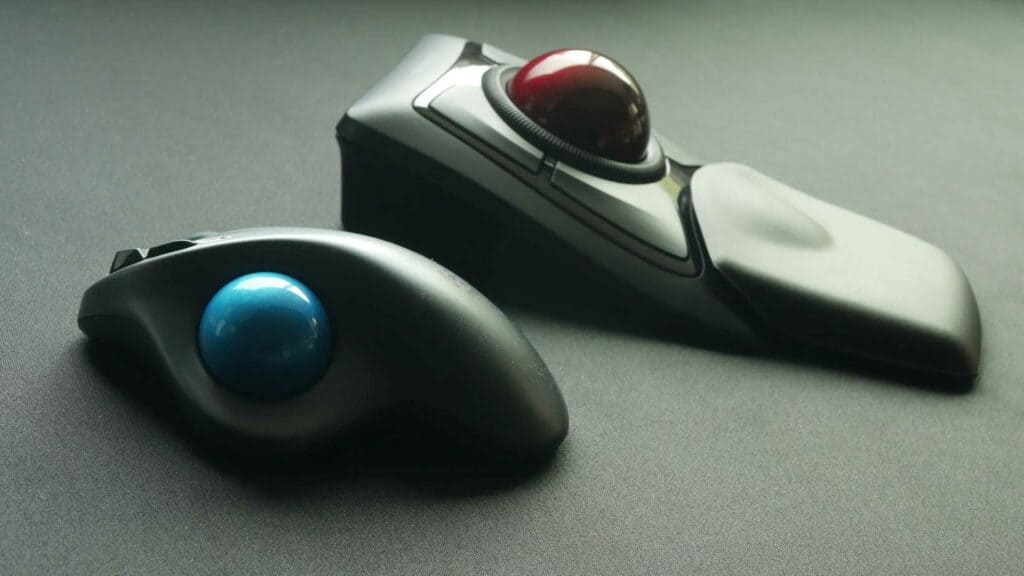 Two different kinds trackballs sitting on a desk