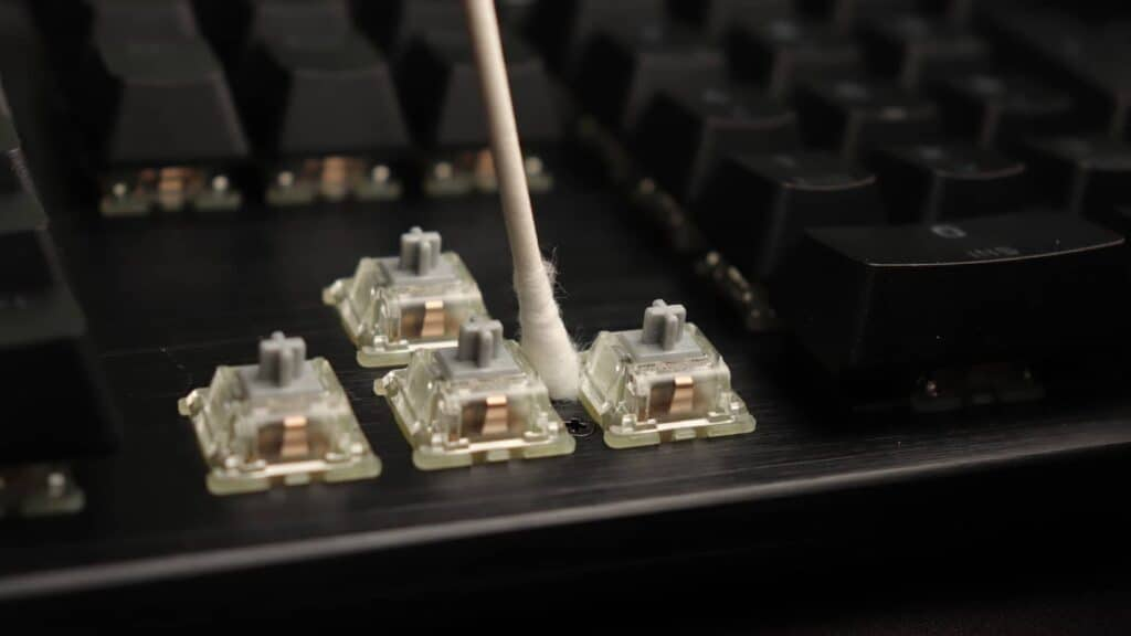 Top plate of mechanical keyboard being cleaned with a cotton swab